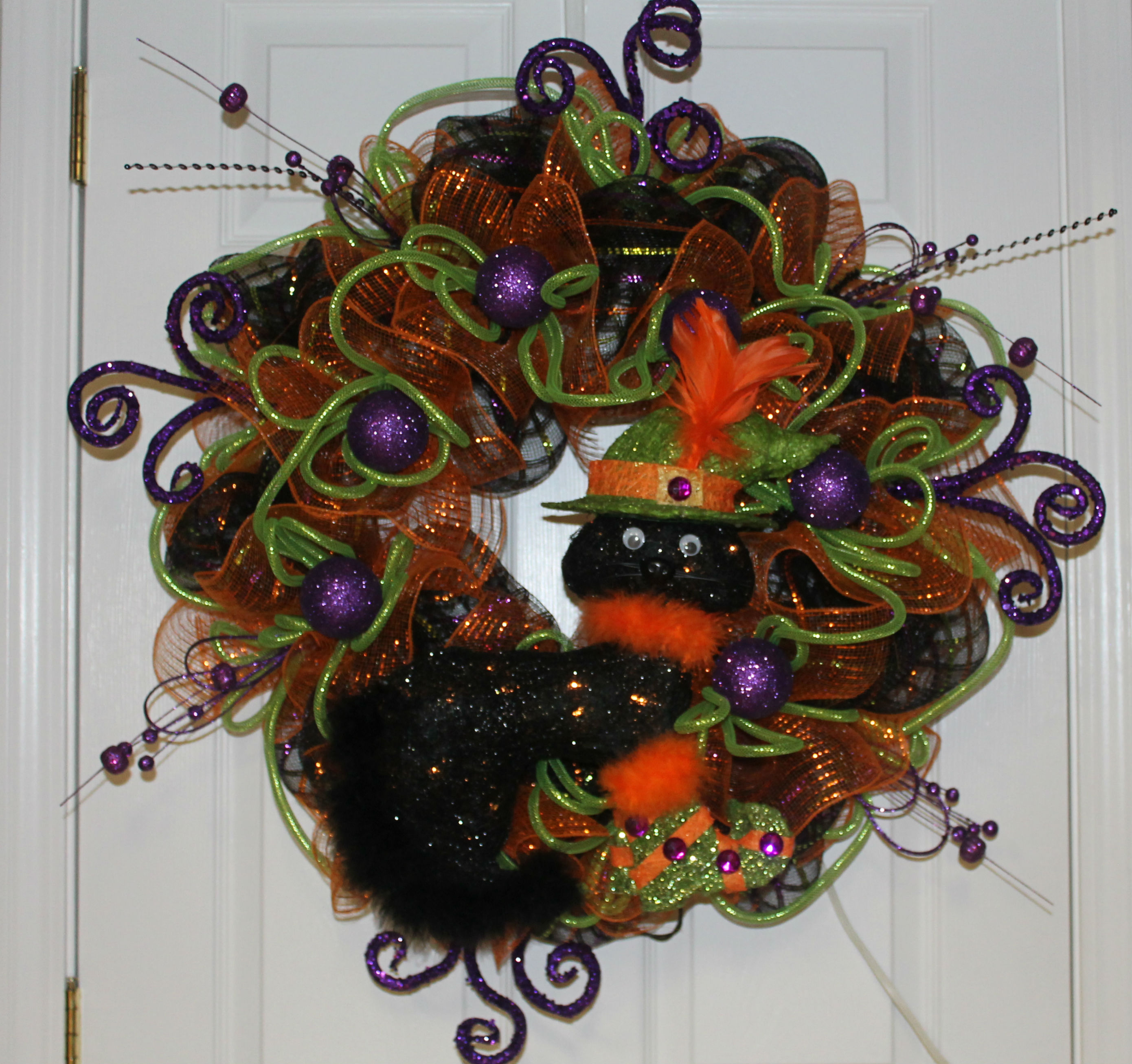This Cat Is Dressed And Ready To Spook You.. This Is A Fun DIY Mesh Wreath  With Color And Glitz And A Dazzling Black Cat Who Is Ready To Celebrate. Nice Ideas