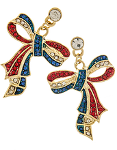 """The patriotic ribbon bow earrings are exceptional and attractive. The striped ribbon is embedded with red, white and blue crystals and is in the shape of a tied bow and have a large crystal at the top of the drop. Gold plate, drop approx. 1.3"""" and has post back."""