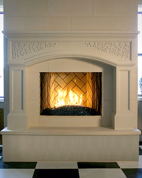 Classic arch design in the header of the stone mantel installed on a raised hearth with extra facing to clad the hearth