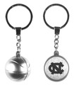 A silver key ring that one side is a basketball and the other shows an interlocking NC.
