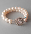 Two strands of white freshwater pearls, 4mm clear Swarovski crystals, 2-strand oval box clasp with a floral terraced design and 44 Swarovski Crystals