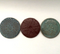 Coasters with various designs shown in quinn's blue, burgundy and turquoise glazes.
