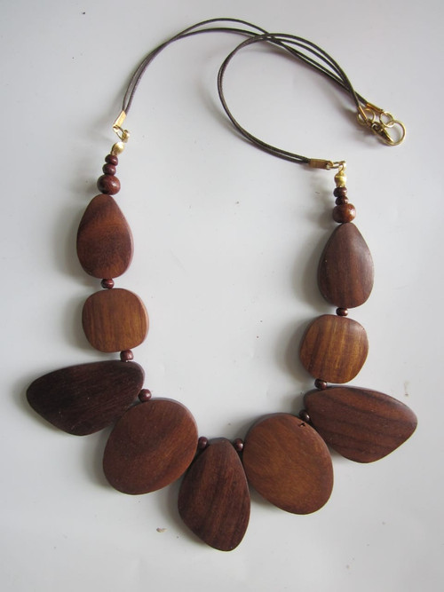 """Picture autumn leaves, four irregularly-shaped pieces of wood form this pendant necklace.   Length 12-14"""" adjustable Each leaf varies in size Thin cord  Wooden pendants Made in India"""
