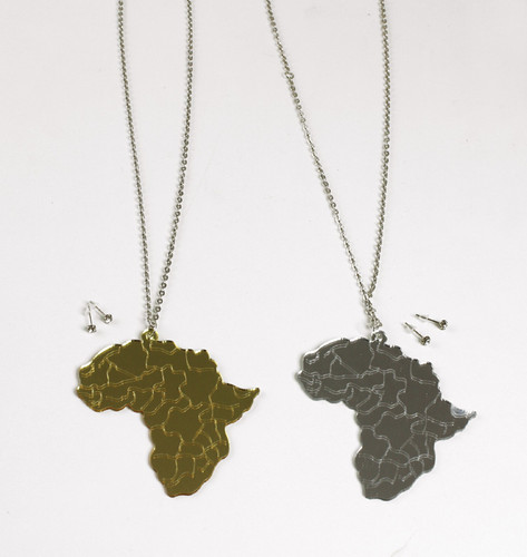 """Africa Map Acrylic Necklace  Glimmering mirror necklaces in the shape of the African continent. Pendant measures 3.5"""" long. 32"""" chain. Available in Gold and Silver."""