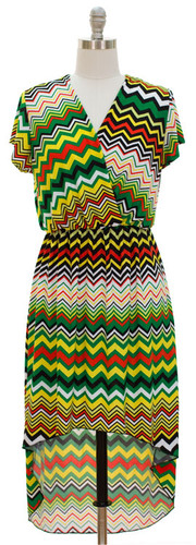"""Rasta High Low Zig Zag Dress features short sleeves with a surplice bodice look, back panel falls to calf and front panel is knee length. Sizes S, M, L, XL  Fits a bust up to 38"""" . Elastic waist for comfort.  Polyester & Spandex material."""