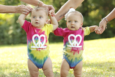 "Our fun ""Peace.Love.Twins"" tie-dye bodysuits are the perfect twin set for summer! It's bursting with color and super soft."