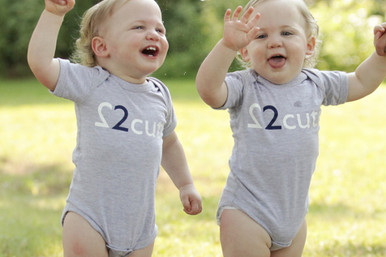 """Our """"2 Cute"""" Infant twin set is available in grey with either a dark navy ink 2 or a pink 2. Also features our logo in dark navy ink on the back."""