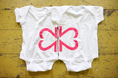 """Our soft white """"Side By Side"""" infant twinset features half of our logo on one infant bodysuit and half of our logo on the other infant bodysuit."""