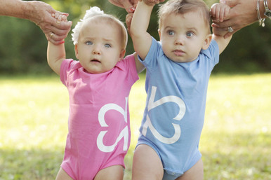 """Our """"Side By Side"""" design infant twin set features half of our logo on one bodysuit and half of our logo on the other infant bodysuit ."""