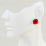 """Red Poppy earrings. Hand patinated bronze with red cast glass petals. 0.5"""" diameter."""