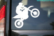 White custom vinyl decal of a motorcycle rider riding a wheelie on a dirt bike.