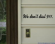 "Custom black vinyl decal of ""We don't dial 911."" applied outside a front door. By Minglewood Trading."