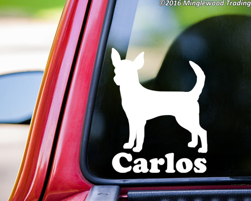 "White custom vinyl decal of a shirt-haired chihuahua with the name ""Carlos"" below. Applied to the rear window of a truck. By Minglewood Trading."