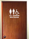 White custom vinyl decal of silhouettes of a woman, a man, and a wheelchair with ALL GENDER BATHROOM below. Applied to a wooden bathroom door. By Minglewood Trading.