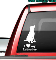 "White custom vinyl decal of a Labrador Retriever sitting with the words ""I love (heart symbol) my Labrador"" beneath. By Minglewood Trading. Applied to the rear window of a pickup truck."