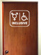 White custom vinyl decal of a Transgender symbol and a wheelchair with INCLUSIVE below. Applied to a white bathroom door. By Minglewood Trading.