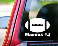 "White custom vinyl decal of a football with the personalized name ""Marcus #4"" below. By Minglewood Trading. Applied to the rear window of a truck."