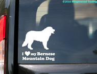 "White custom vinyl decal of a Bernese Mountain Dogsitting with the words ""I love (heart symbol) my Bernese Mountain Dog"" beneath. By Minglewood Trading. Applied to the rear window of an truck."