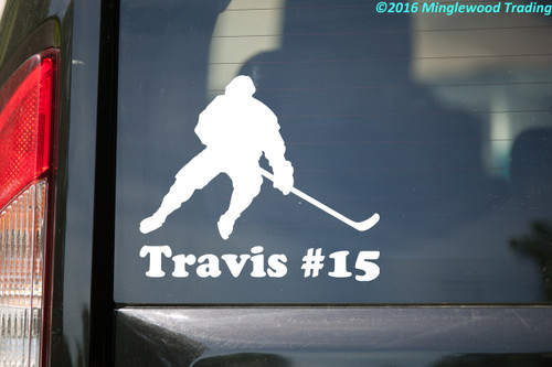 White custom vinyl decal sticker of a broomball player with the name Travis and #15 underneath, by Minglewood Trading. Applied to the rear window of a suv.