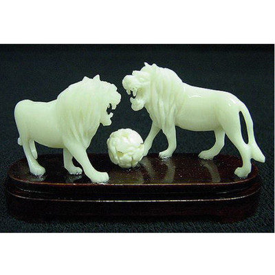 hand carved bone lions playing with ball