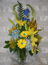 Cute As A Button New Baby Boy Flower Arrangement from Enchanted Florist. A perfect vase of mixed flowers to celebrate that special new bundle of joy. Includes blue hydrangeas and delphinium, yellow lilies & gerberas, and other flowers and is accented with adorable buttons to celebrate your new arrival. SKU RM324