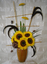 "Bellini Sunflower Bouquet with Bamboo Trellis by Enchanted Florist Pasadena - This contemporary and stylish arrangement is sure to catch anyone's eye. A unique masterpiece accented with stones, wire, and feathers. Includes sunflowers and a bamboo trellis. Approximately 30""H x 16W.  SKU RM216"