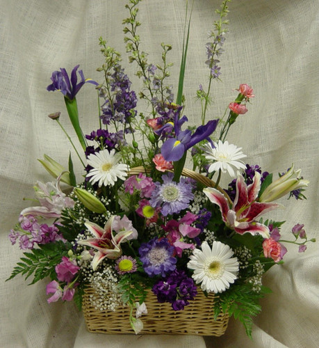 "Spring Garden Funeral Basket by Enchanted Florist - This lovely spring garden basket for a funeral is full of spring flowers and is appropriate for the sympathy service or family home. Spring time flowers include iris, white gerbera daisies, stargazer lilies, lavender larkspur, baby's breath and more to complete a cheerful basket of flowers. Approximately 24"" W x 30"" H SKU RM503"
