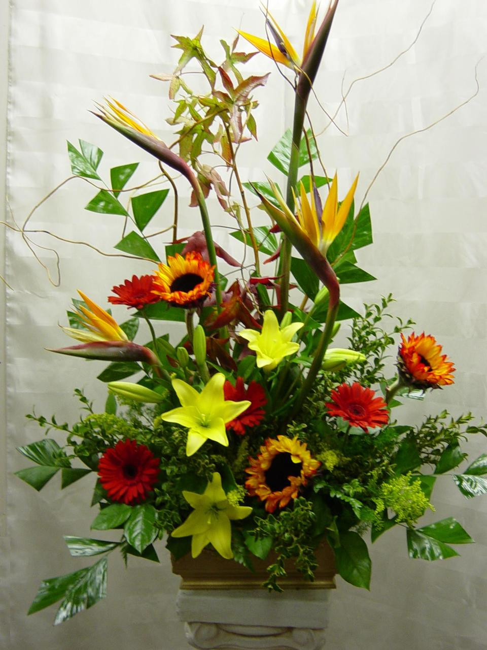 Bright and lovely funeral flowers sunflowers lilies tropicals lifes celebration funeral arrangement by enchanted florist pasadena tx bright and beautiful funeral flowers arranged izmirmasajfo