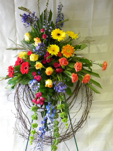 Eternal Sunshine Grapevine Wreath by Enchanted Florist Pasadena - a custom grapevine funeral wreath with bright colored flowers including yellow gerbera daisies, blue delphinium, yellow roses, and more. Funeral flowers delivered to local Houston and Pasadena funeral homes. RM510