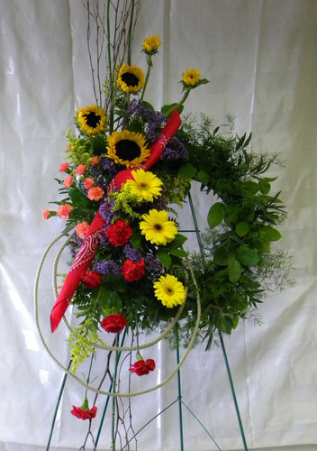 Texas Pride Funeral Wreath by Enchanted Florist Pasadena TX - a floral wreath covered in beautiful colorful flowers including happy sunflowers and a red bandana. Sympathy flowers delivered to local funeral homes in Houston TX and Pasadena TX  RM511