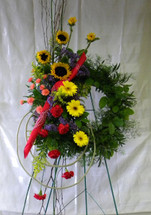 Texas Pride Wreath by Enchanted Florist Pasadena TX - a floral wreath covered in beautiful colorful flowers including happy sunflowers and a red bandanna. Sympathy flowers delivered to local funeral homes in Houston TX and Pasadena TX  RM511