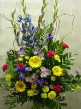 Spring Time Funeral Flower Basket by Enchanted Florist Pasadena TX - a lush funeral arrangement of purple gladiolas, blue delphinium, yellow gerbera daisies, and hot pink carnations. Can be delivered same day or next day to most Clear Lake and Houston area funeral homes. RM512