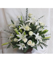 White Serenity Urn Funeral Flowers Arrangement are all white funeral arrangements of flowers in a classic heritage urn and includes white lilies, white roses, and white carnations and eucalyptus accented with spiral eucalyptus. Order online now for a funeral floral delivery in Houston TX, Pasadena TX, Pearland TX and surrounding areas. RM531