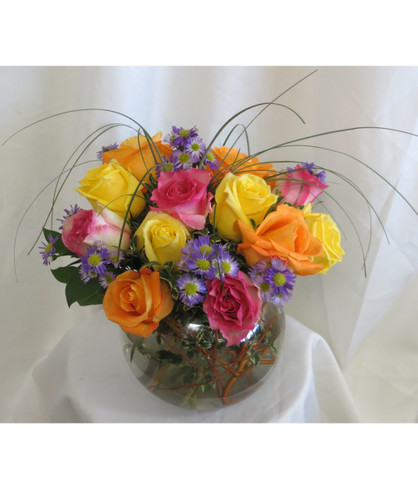 Tropical Paradise Bright Colored Bowl of Roses by Enchanted Florist Pasadena TX. A dozen beautifully arranged bright colored roses in a clear glass bowl including hot pink, orange, and yellow roses. Order now for your Houston flower delivery by a real florist. Our family owed flower shop delivers daily. Call (832)850-7677 RM360