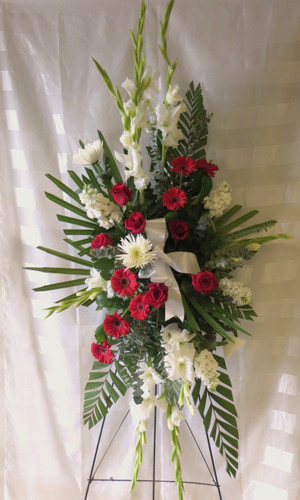 Starry Night Standing Spray by Enchanted Florist Pasadena TX. A beautiful a classic combination of red roses, white gladiolas, red gerbera daisies, white spider flowers and white stock together in a standing funeral spray of flowers for a funeral service to many of the funeral homes in Houston TX. RM518
