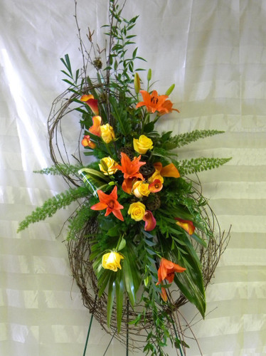 """Autumn Harvest Grapevine Funeral Flower Wreath by Enchanted Florist TX. Send unique and creative funeral flowers with this grapevine flower wreath standing spray. A custom creation by our talented designers. Sympathy flowers include orange lilies, yellow roses, and orange mini calla lilies with tropical foliages arranged on this grapevine wreath. Approximately 70""""H x 28""""W. (size does not include stand)  SKU RM519"""