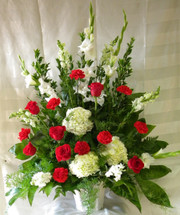 """Sweet Devotions Red and White Funeral Flowers by Enchanted Florist Pasadena TX. Send a sweet sympathy flower arrangement of traditional red carnations, classic red roses, white gladiolas, white snapdragons, and white hydrangeas in a white funeral container.  Approximately 34""""H x 26""""W (size does not include easel)  SKU RM520"""