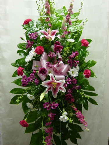 ink Perfection Standing Spray by Enchanted Florist Pasadena TX. A beautiful pink spray of sympathy flowers in an easel for the women you will miss. Flowers included are fragrant stargazer lilies, pink larkspur, hot pink carnations, purple carnations, and white daisies. Floral delivery in Houston TX and surrounding areas. RM522