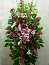 Pink Perfection Standing Spray by Enchanted Florist Pasadena TX. Flowers included are fragrant stargazer lilies, pink larkspur, hot pink carnations, purple carnations, and white daisies. Pink funeral flowers delivery in Houston TX and surrounding areas. RM522