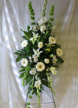 Peaceful Embrace White Flowers Standing Spray by Enchanted Florist Pasadena TX. All white flowers including white gerbera daisies, white roses, green bells of ireland, fragrant white lilies and white alstroemeria. White funeral flowers. RM523
