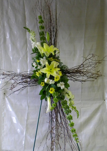 Lovely Birch Sympathy Cross by Enchanted Florist Pasadena TX. This birch cross includes yellow lilies, white snaps, and yellow daisies and more for this sympathy floral delivery. RM524