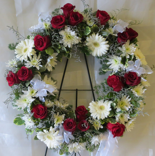 Divine Wreath Sympathy Flowers by Enchanted Florist Pasadena TX. Simply divine, red and white flowers together classically designed in a funeral wreath. Flowers include traditional red roses along with white gerbera daisies and sheer white bows placed together are a great way to remember a loved one. RM526