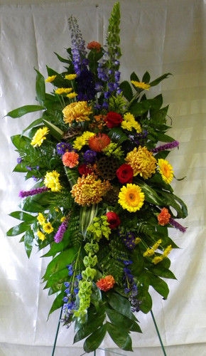 "Bronze Memory Masculine Fall Sympathy Standing Spray by Enchanted Florist Pasadena TX. This lovely masculine sympathy spray of fall themes flowers includes football mums, protea, bells of Ireland, delphinium, red roses and so much more. Approx 56""H x 26""W (size does not include stand)  SKU RM527"
