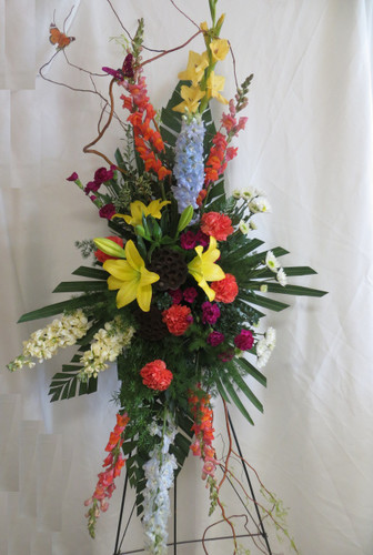 Heavenly Solace Funeral Standing Spray by Enchanted Florist Pasadena TX. Delivery of beautiful funeral flowers to local Houston and Pasadena funeral homes and churches. Same day funeral flower delivery. Yellow lilies, orange carnations, fragrant yellow stock. RM535