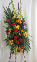 Spectacular Sunset Sympathy Spray of Flowers by Enchanted Florist Pasadena TX. Bright bold colors in a heartwarming sympathy standing spray and includes yellow gladiolas, red carnations, purple liatris, yellow daisies, orange spray roses, and purple daisies. RM537