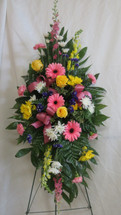 Beautiful Farewell Pink Sympathy Spray of Flowers by Enchanted Florist Pasadena TX.  A mixed color spray of sympathy flowers in a standing spray and includes pink gerbera daises, yellow roses, pink larkspur and yellow snapdragons. RM539