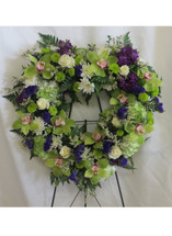 With All My Heart Funeral Wreath by Enchanted Florist Pasadena TX. Heart shaped funeral wreath of sympathy flowers including green cymbidium orchids, white roses, green hydrangeas, white cushions, and purple stock. Heart shaped funeral flowers. RM540