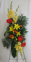 "Sunset Tribute Yellow Funeral Spray of Flowers by Enchanted Florist Pasadena TX. Funeral flowers include yellow gladiolas, yellow lilies, orange gerbera daisies, orange spray roses and exotic green foliages. Arrives hand delivered by our flower professionals on a wire sympathy easel. Approximately 54""H x 28""W.   SKU RM541"