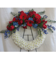 """Stars and Stripes Patriotic Funeral Wreath Flowers by Enchanted Florist. Sympathy flowers include red roses, red gerberas daisies, blue hydrangeas and blue delphinium (similar to blue bonnets). Send a patriotic sympathy flower wreath delivery today to most Houston and Pasadena funeral homes. Approximately 23""""H x 30""""W (does not include stand size) SKU RM542"""