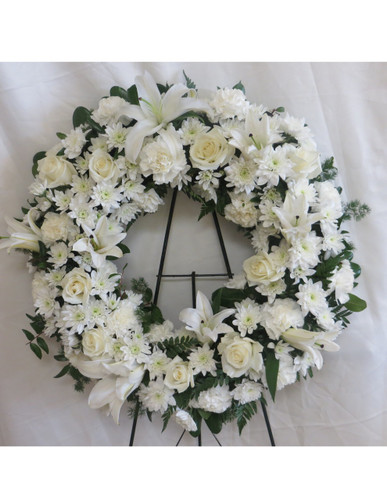 Sincere Serenity Funeral Wreath by Enchanted Florist Pasadena TX. An all white sympathy flower wreath full of white lilies, white roses, white carnations, and white cushions. RM543